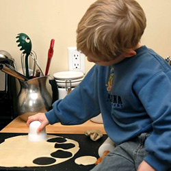 child helping bake cookies, using cookie cutters