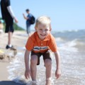 summer fun at the beach, boy playing in the waves
