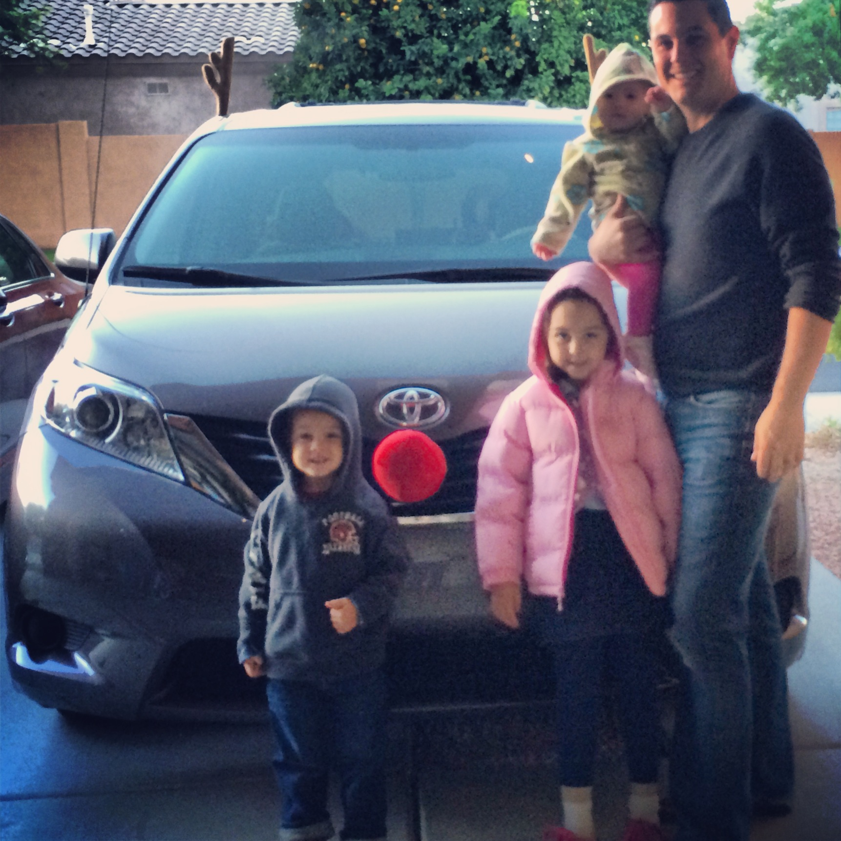 family with minivan dressed as reindeer
